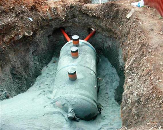 Фото септика на бетонном «якоре» в процессе засыпания песком с цементом